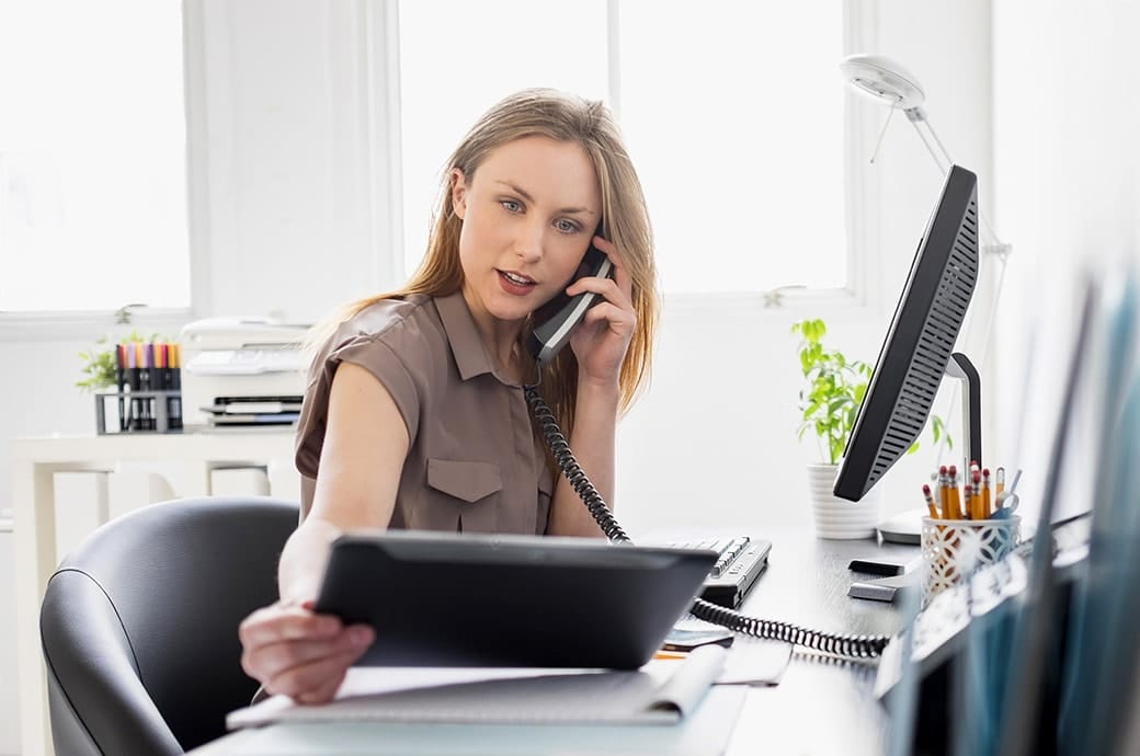 A woman at her desk in the office looking at a tablet while on the phone